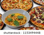 pizza and pasta on a table  | Shutterstock . vector #1153494448