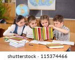 Four elementary aged pupils reading book in classroom - stock photo