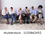bored people sitting in a row... | Shutterstock . vector #1153862452