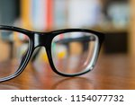 eyeglasses on a table with... | Shutterstock . vector #1154077732