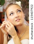 Young beautiful bride in necklace wears earrings - stock photo
