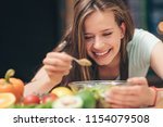 smiling young girl cooking in... | Shutterstock . vector #1154079508
