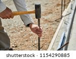 Man Using A Sledge Hammer To...