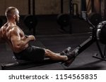 full length side view shot. a fit young man working out with a indoor rower. lifestyle and hobby concept