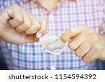 condom ready to use in man hand ... | Shutterstock . vector #1154594392