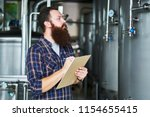 man at brewery taking notes on... | Shutterstock . vector #1154655415