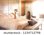 Stock photo young woman in bathrobe lying on the bed in the beautiful hotel room on sunny morning 1154713798