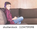 boy relaxing at home while...   Shutterstock . vector #1154759398