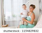 mom with the baby one year old... | Shutterstock . vector #1154829832