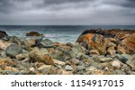 Boulders And Moody Sky By The...