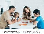 parents helping children with... | Shutterstock . vector #1154933722