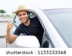 Stock photo young asian man smiling and showing thumb up in his car 1155233368