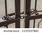 rusty chain at the gate | Shutterstock . vector #1155337882