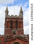 Small photo of Bell tower of Crediton Parish Church of the Holy Cross and the Mother of Him Who Hung thereon in spring sunny day, Devon, UK, March 4, 2017