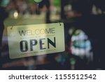 Welcome open sign on door of...