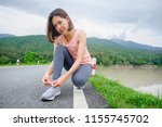 young fitness woman tying... | Shutterstock . vector #1155745702