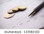 Pen And Coins On Financial...