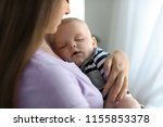 mother with her sleeping baby...   Shutterstock . vector #1155853378