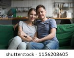 Small photo of Portrait of smiling millennial couple embracing looking at camera at home, cheerful happy husband and wife new homeowners or tenants hugging sitting on sofa in the kitchen showing care and support