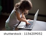 Small photo of Curious smart little girl typing on laptop alone, clever cute child using computer online without permission, forbidden internet content parental protection, pc control and security for kid concept