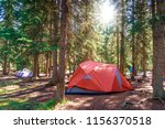Morning sunrise over camping tent in the summer wilderness of Banff National Park in Canada with surrounding pine trees. - stock photo