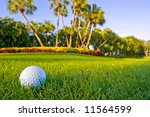 golf ball on fairway of lovely tropical golf course with dewy grass and blue sky - stock photo
