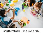 Stock photo high angle view of group of schoolgirls taking lunch at school cafeteria 1156615702