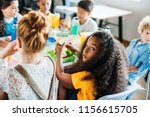 Stock photo african american schoolgirl taking lunch at school cafeteria with her classmates and looking at 1156615705