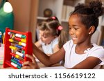 Two Little Girls Sitting At A...