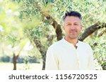 olive trees. handsome man... | Shutterstock . vector #1156720525