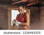 female boxer wearing strap on... | Shutterstock . vector #1156965325