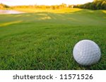 golf ball resting on bunker of lovely golf course with early morning sun hitting the fairway - stock photo