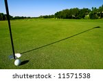 golf ball near hole and pin of lovely tropical golf course with clear blue sky - stock photo