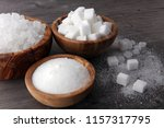 Small photo of Bowl with white sand, crystal and lump sugar on wooden background.