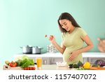 Young Pregnant Woman Eating...