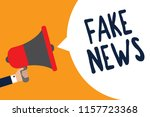 writing note showing fake news. ... | Shutterstock . vector #1157723368