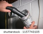 Vacuum cleaning a flexible aluminum dryer vent hose, to remove lint and prevent fire hazard.