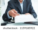 man in a suit offers to sign a... | Shutterstock . vector #1159185922
