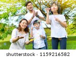 asian family blowing bubbles in ... | Shutterstock . vector #1159216582