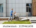 woman in a wheelchair using a... | Shutterstock . vector #1159461658