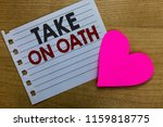 Small photo of Conceptual hand writing showing Take On Oath. Business photo showcasing A solemn appeal to a deity Speak the truth Make a Promise Notebook paper Romantic ideas heart feelings Wooden table.