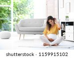 happy pregnant woman sitting on ... | Shutterstock . vector #1159915102