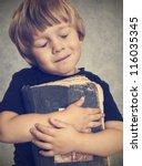 Little Boy Hugging An Old Book...