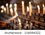 Woman Lighting Prayer Candle...