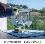 waiter pouring white wine on... | Shutterstock . vector #1161019138