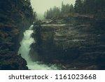 Raw Foggy Norwegian Waterfalls Landscape. Rushing Water Between the Granite Rocks. Western Norway, Europe. - stock photo