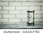 hourglass on a brick background | Shutterstock . vector #1161317782