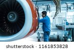 Stock photo aircraft maintenance mechanic inspects and tunes plane engine in a hangar 1161853828