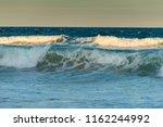 waves in sunset on gold  oast ... | Shutterstock . vector #1162244992