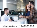 happy buyers talking with car... | Shutterstock . vector #1162389235